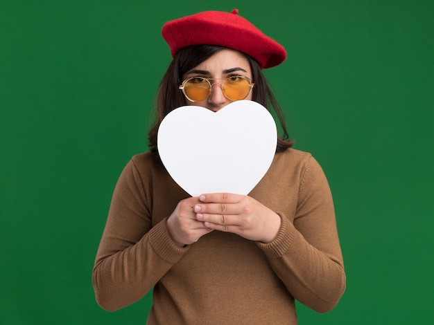 Tevreden jong vrij kaukasisch meisje dat met barethoed in zonglazen hartvorm voor gezicht op groen houdt