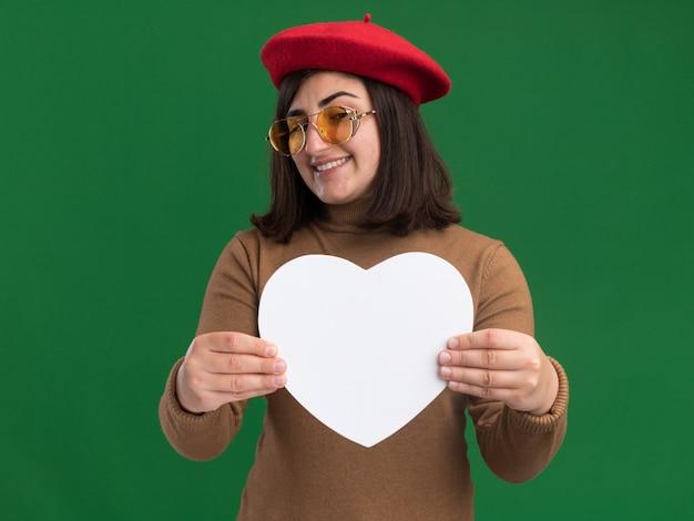 Tevreden jong vrij kaukasisch meisje die met barethoed in zonglazen houden en hartvorm op groen bekijken