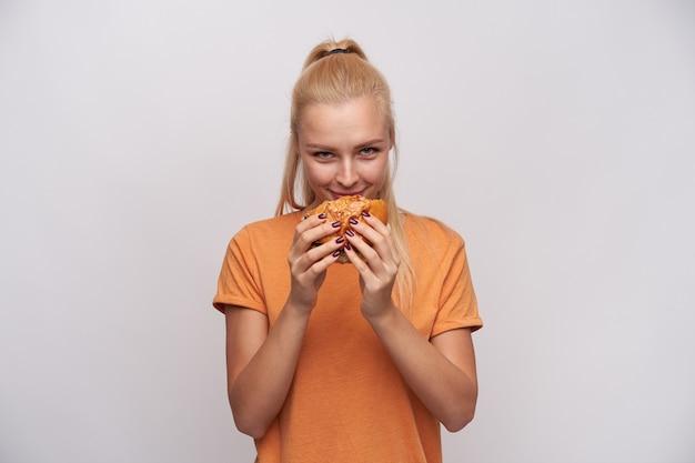 Tevreden jonge aantrekkelijke blonde vrouw met paardenstaart verse hamburger verrukken en vrolijk kijken naar camera, oranje t-shirt dragen terwijl staande tegen een witte achtergrond