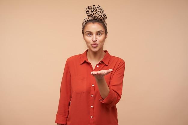 Tevreden jonge aantrekkelijke brunette met groene ogen die haar lippen tuit terwijl ze een luchtkus aan de voorkant verzendt, staande over beige muur met opgeheven hand
