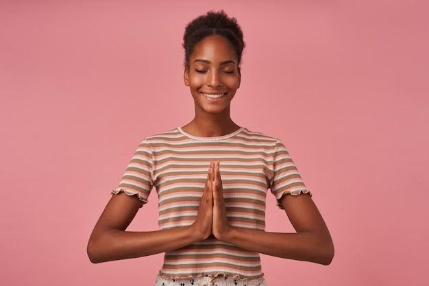 Tevreden jonge aantrekkelijke brunettened vrouw die haar ogen gesloten houdt terwijl ze breed glimlacht en opgeheven handen samen vouwt, staande over de roze muur