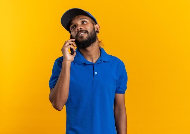 Tevreden jonge afro-amerikaanse bezorger die aan de telefoon praat en omhoog kijkt geïsoleerd op een oranje achtergrond met kopieerruimte