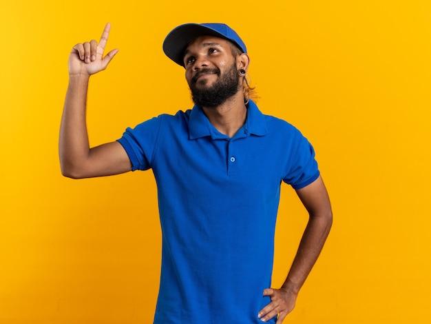 Tevreden jonge afro-amerikaanse bezorger die omhoog wijst op een oranje muur met kopieerruimte