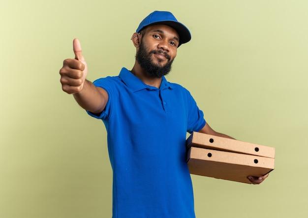 Tevreden jonge afro-amerikaanse bezorger die pizzadozen vasthoudt en omhoog steekt geïsoleerd op olijfgroene muur met kopieerruimte