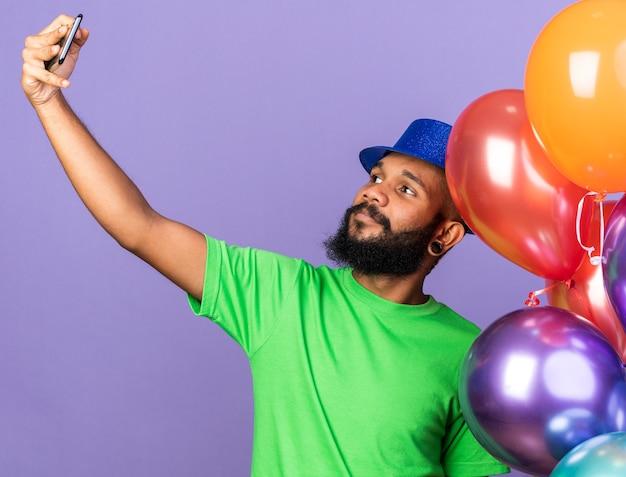 Tevreden jonge afro-amerikaanse man met een feesthoed met ballonnen en een selfie geïsoleerd op een blauwe muur