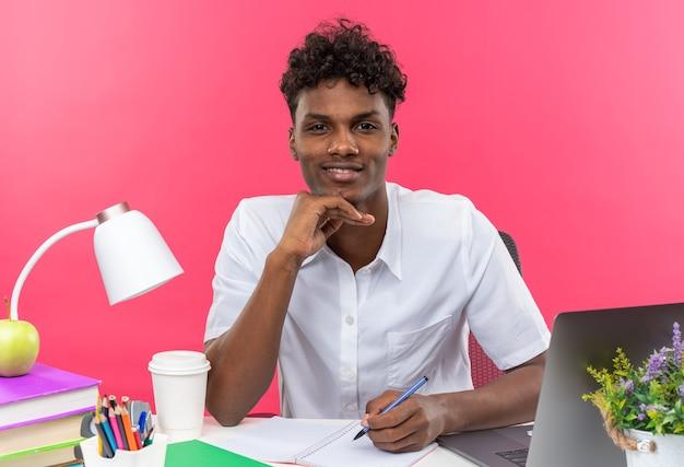 Tevreden jonge afro-amerikaanse student die aan een bureau zit met schoolhulpmiddelen die zijn hand op zijn kin leggen, geïsoleerd op een roze muur