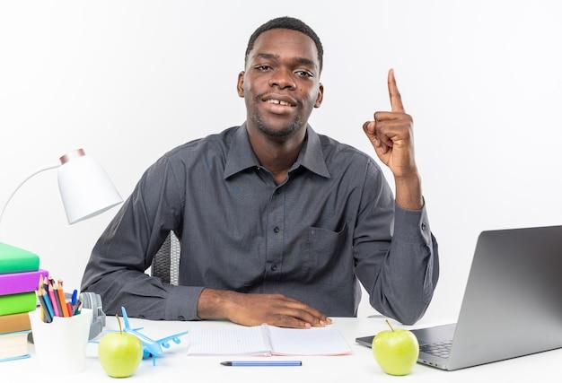 Tevreden jonge afro-amerikaanse student die aan het bureau zit met schoolhulpmiddelen die naar boven wijzen