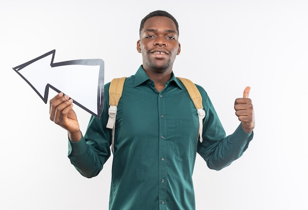 Tevreden jonge afro-amerikaanse student met rugzak met pijl en duim omhoog