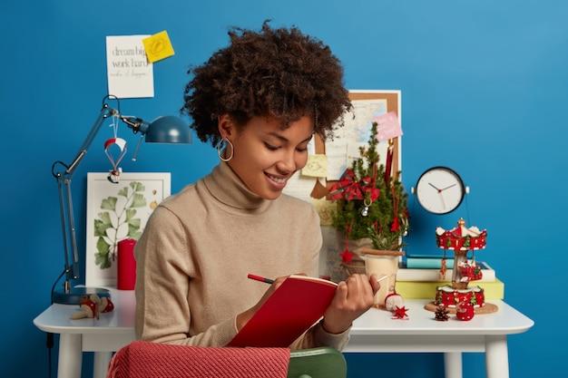Tevreden jonge afro-amerikaanse vrouw schrijft notities in dagboek, bereidt zich voor op examens op kerstavond, vormt in moderne studeerkamer