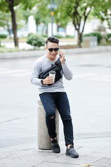 Tevreden jonge aziatische man met heuptas die op een kleine straatpaal tegen de weg zit en telefonisch praat terwijl hij koffie drinkt