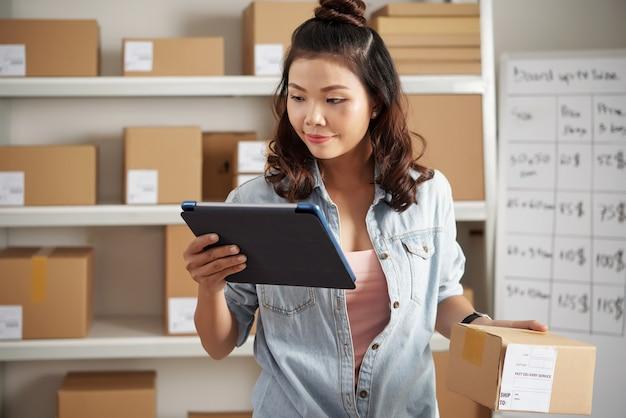 Tevreden jonge aziatische vrouw die digitale tablet gebruikt terwijl ze het aantal pakketten op het postkantoor controleert