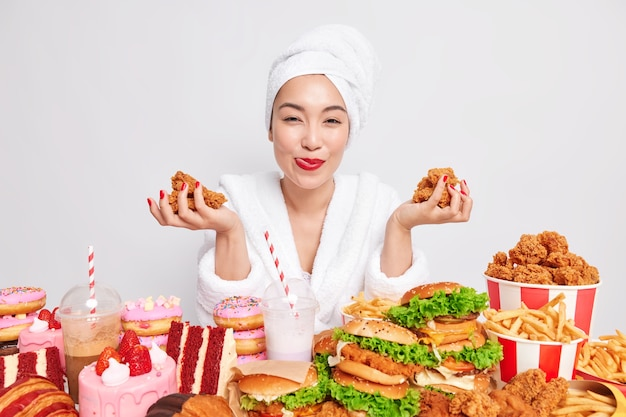 Tevreden jonge aziatische vrouw met rode lippenstiftmanicure houdt heerlijke nuggets vast die verslaafd zijn aan fastfood