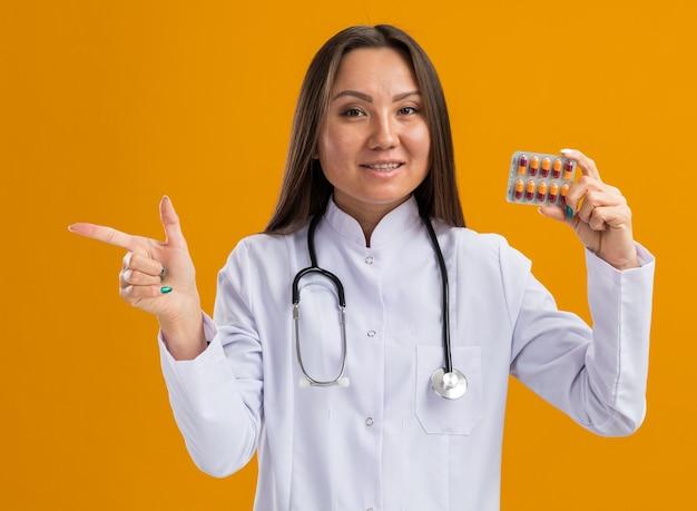 Tevreden jonge aziatische vrouwelijke arts die medische mantel en stethoscoop draagt die een pakje medische capsules toont aan de camera die naar de voorkant kijkt en naar de zijkant wijst die op een oranje muur wordt geïsoleerd