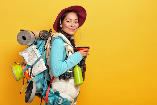Tevreden jonge aziatische vrouwelijke reiziger stopt onderweg om koffiepauze te houden, draagt hoed en casual outfit, poseert met rugzak, heeft een lange reis, verkent nieuwe plaatsen, houdt van reizen