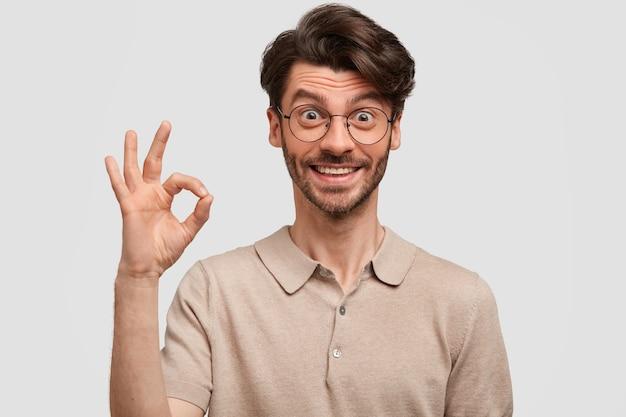 Tevreden jonge bebaarde hipster toont ok teken, toont zijn instemming, bewijst dat alles geweldig is
