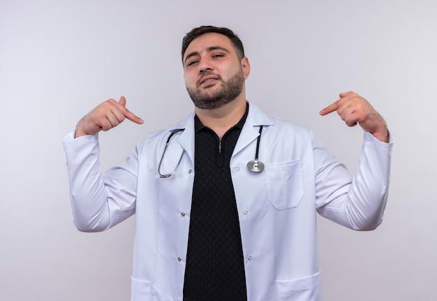 Tevreden jonge bebaarde mannelijke arts die witte jas draagt met een stethoscoop die naar zichzelf wijst op zoek zelfverzekerd