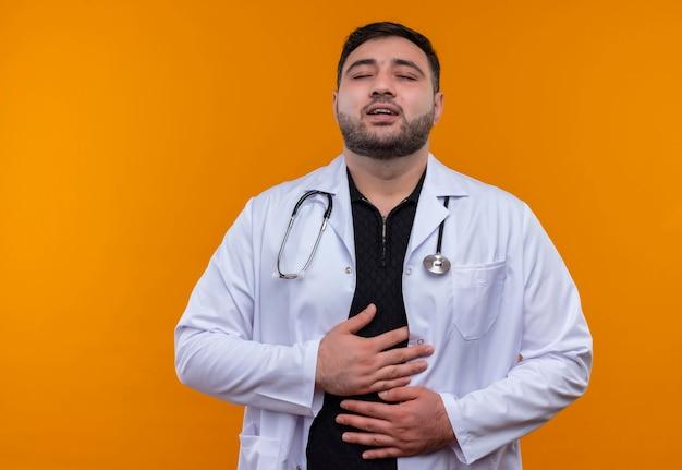 Tevreden jonge bebaarde mannelijke arts die witte jas met stethoscoop draagt met gesloten ogen die zijn buik aanraken