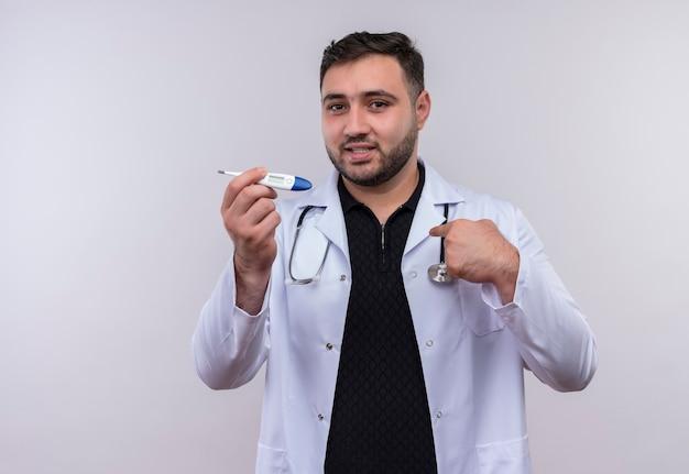 Tevreden jonge bebaarde mannelijke arts die witte laag met stethoscoop draagt die digitale thermometer houdt die zelfverzekerd glimlacht richtend naar zichzelf