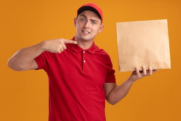 Tevreden jonge bezorger die uniform met pet draagt en wijst naar papieren voedselpakket geïsoleerd op een oranje muur