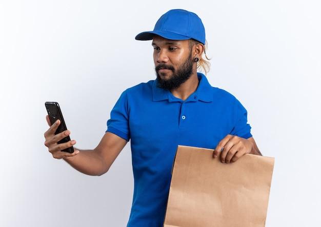 Tevreden jonge bezorger die voedselpakket vasthoudt en naar telefoon kijkt die op een witte muur met kopieerruimte wordt geïsoleerd