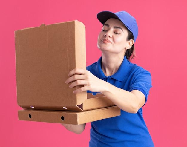 Tevreden jonge bezorger in uniform en pet met pizzapakketten die er een openen en eraan snuiven met gesloten ogen geïsoleerd op roze muur