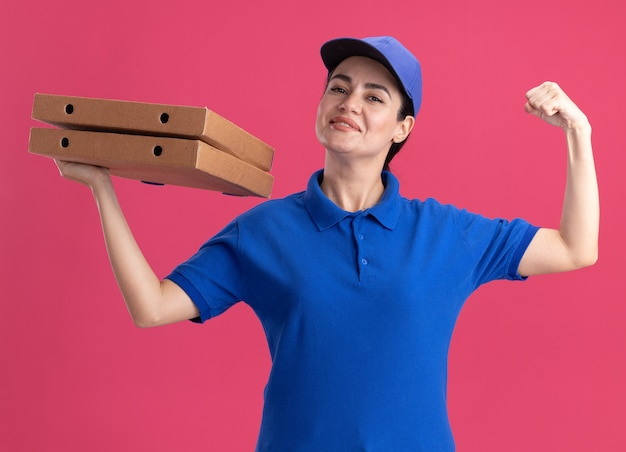 Tevreden jonge bezorger in uniform en pet met pizzapakketten die naar voren kijken en een sterk gebaar doen geïsoleerd op roze muur