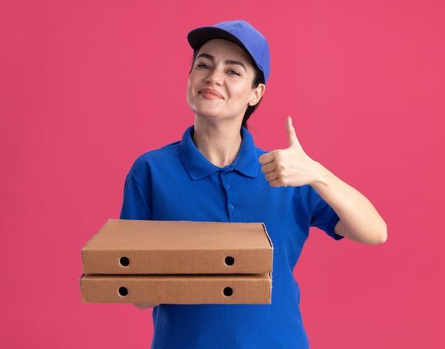 Tevreden jonge bezorger in uniform en pet met pizzapakketten met duim omhoog