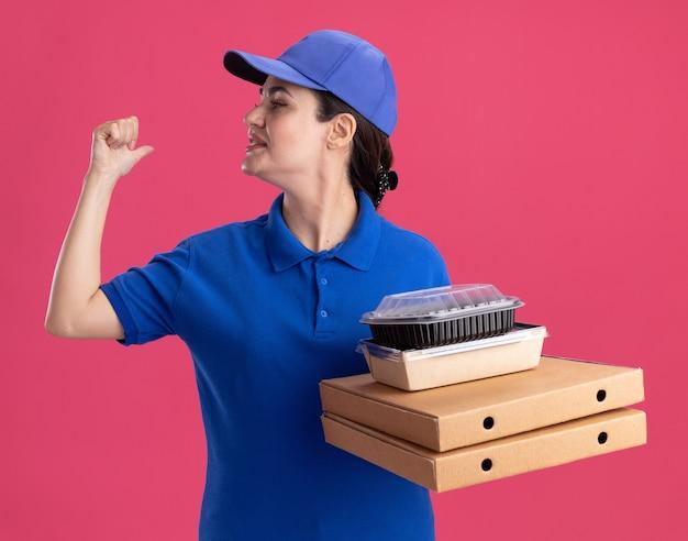 Tevreden jonge bezorger in uniform en pet met pizzapakketten met papieren voedselpakket en voedselcontainer erop kijkend naar de zijkant die naar achteren wijst