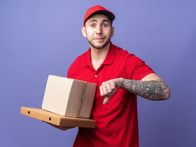 Tevreden jonge bezorger in uniform met dop die doos op pizzadozen vasthoudt