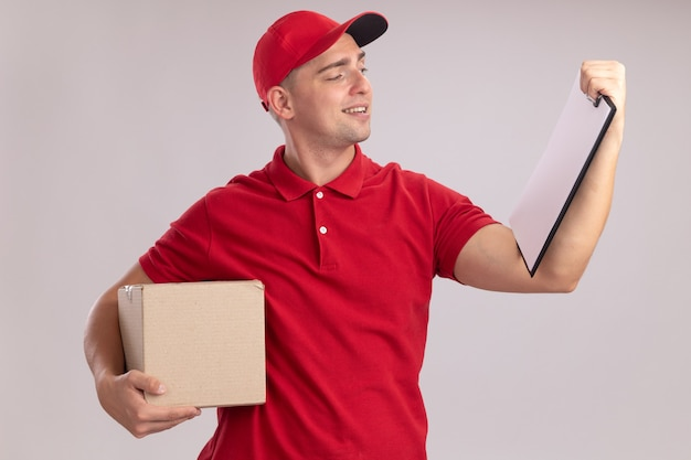 Tevreden jonge bezorger in uniform met dop die doos vasthoudt en naar klembord in zijn hand kijkt, geïsoleerd op een witte muur white