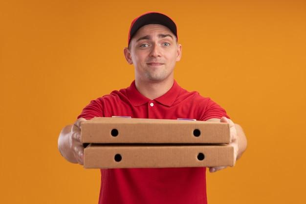 Tevreden jonge bezorger in uniform met pet die pizzadozen vasthoudt op camera geïsoleerd op oranje muur
