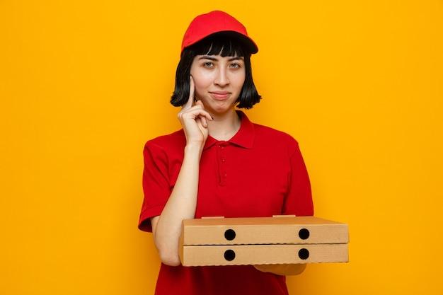 Tevreden jonge blanke bezorger die pizzadozen vasthoudt en naar de voorkant kijkt