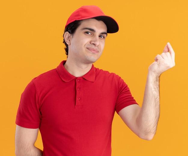 Tevreden jonge blanke bezorger in blauw uniform en pet die de hand achter de rug houdt en een tipgebaar doet geïsoleerd op een oranje muur