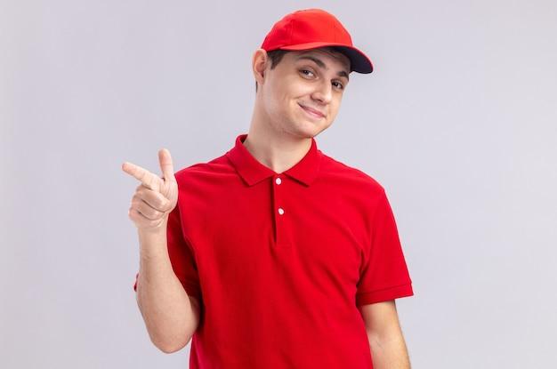 Tevreden jonge blanke bezorger in rood shirt wijzend naar de zijkant
