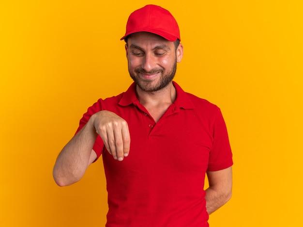 Tevreden jonge blanke bezorger in rood uniform en pet die hand achter de rug houdt alsof hij iets vasthoudt terwijl hij naar zijn hand kijkt geïsoleerd op een oranje muur