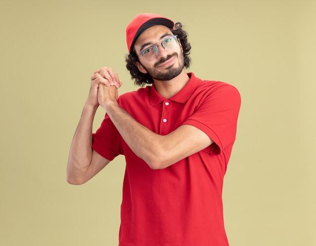 Tevreden jonge blanke bezorger in rood uniform en pet met een bril die een winnend gebaar doet