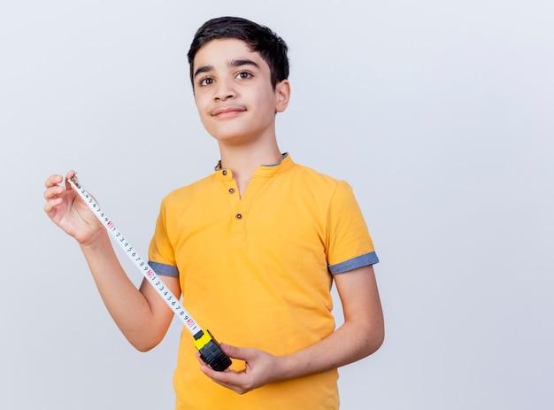 Tevreden jonge blanke jongen die recht kijkt die de meter van de holdingsband op witte achtergrond met exemplaarruimte wordt geïsoleerd