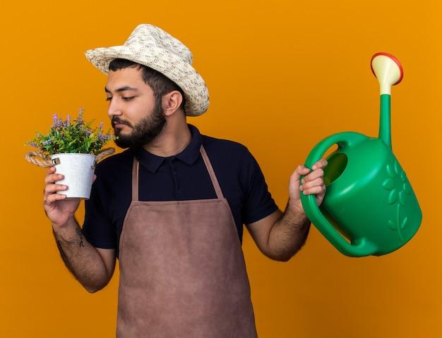 Tevreden jonge blanke mannelijke tuinman draagt ?? tuinieren hoed met gieter en snuift bloemen in bloempot geïsoleerd op oranje muur met kopie ruimte