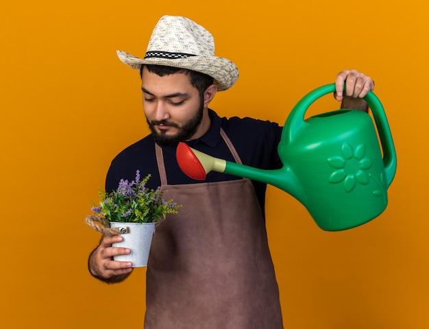 Tevreden jonge blanke mannelijke tuinman met tuinhoed die doet alsof hij bloemen water geeft in een bloempot met gieter geïsoleerd op een oranje muur met kopieerruimte