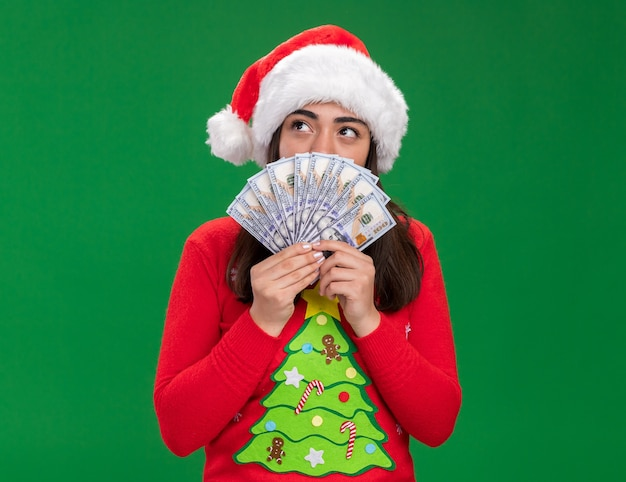 Tevreden jonge blanke meisje met kerstmuts houdt geld kijken kant geïsoleerd op groene achtergrond met kopie ruimte