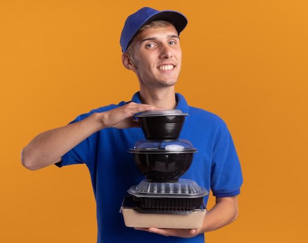 Tevreden jonge blonde bezorger houdt voedselcontainers op voedselpakket geïsoleerd op een oranje muur met kopieerruimte