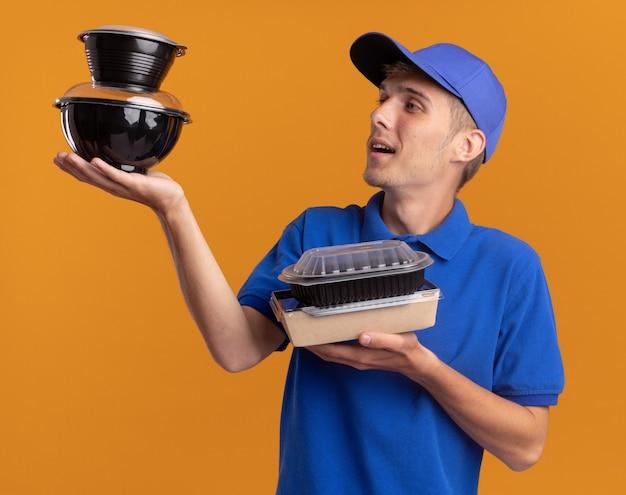 Tevreden jonge blonde bezorger houdt voedselcontainers vast en kijkt naar plastic verpakkingen op oranje
