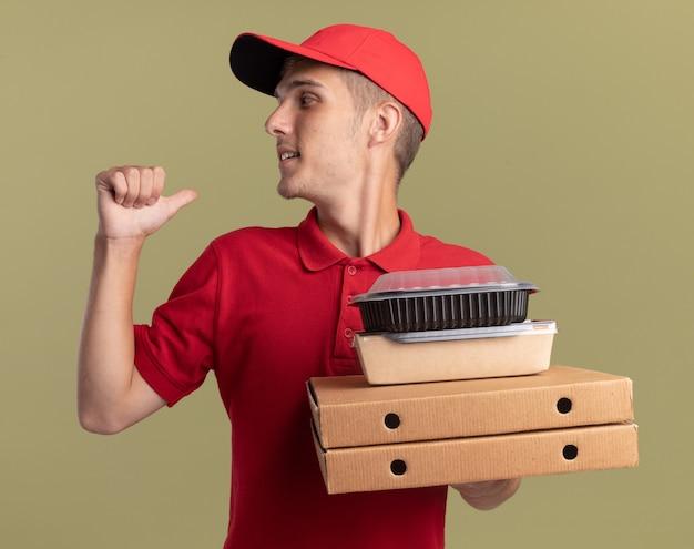 Tevreden jonge blonde bezorger houdt voedselpakketten vast op pizzadozen en wijst terug op olijfgroen