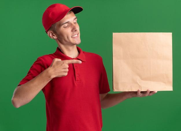 Tevreden jonge blonde bezorger kijkt en wijst op papierpakket op groen