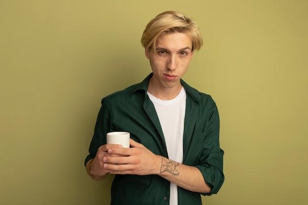 Tevreden jonge blonde kerel die een groene kop van de t-shirtholding thee draagt die handen kruist
