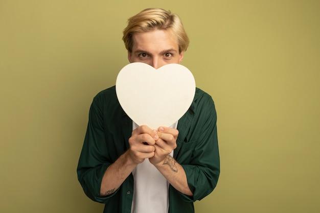 Tevreden jonge blonde kerel die groene t-shirt draagt ?? die de doos van de hartvorm houdt