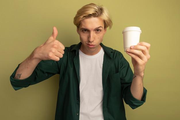 Tevreden jonge blonde kerel die groene t-shirt draagt die kop thee houdt en duim toont