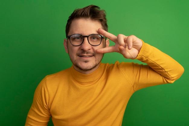 Tevreden jonge blonde knappe man met een bril die op zoek is naar een v-tekensymbool in de buurt van een oog geïsoleerd op een groene muur