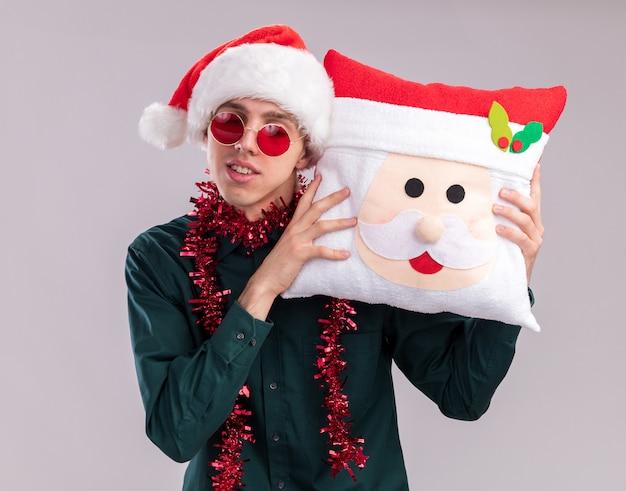 Tevreden jonge blonde man met kerstmuts en bril met klatergoudslinger om de nek met een kussen van de kerstman die het hoofd ermee aanraakt met gesloten ogen geïsoleerd op witte achtergrond
