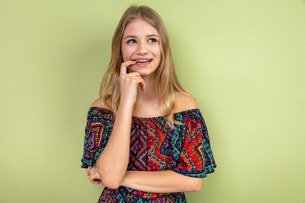 Tevreden jonge blonde slavische meid die haar nagel bijt en omhoog kijkt